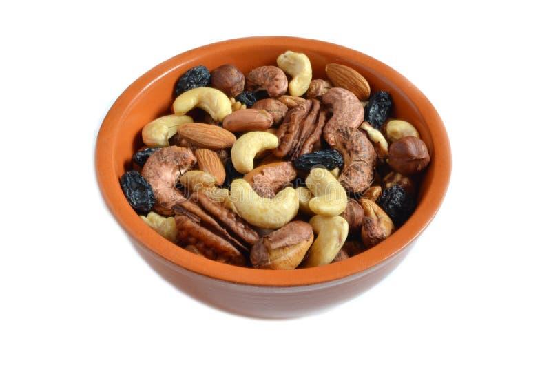 Raisins secs Nuts dans la tasse d'argile sur le fond blanc d'isolat image stock