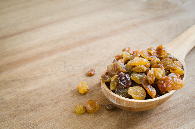 Raisins secs organiques secs dans une cuillère en bois sur le fond rustique Plan rapproché images stock