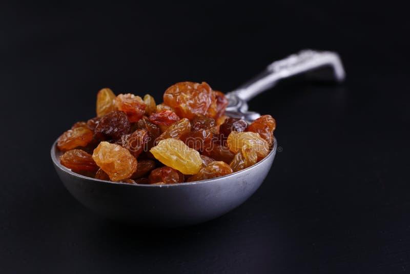 Raisins in steel spoon stock images