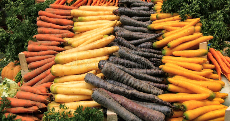 Raizes orgânicas dos vegetais em um mercado do alimento: cenouras, cenouras pretas, nabos imagem de stock royalty free