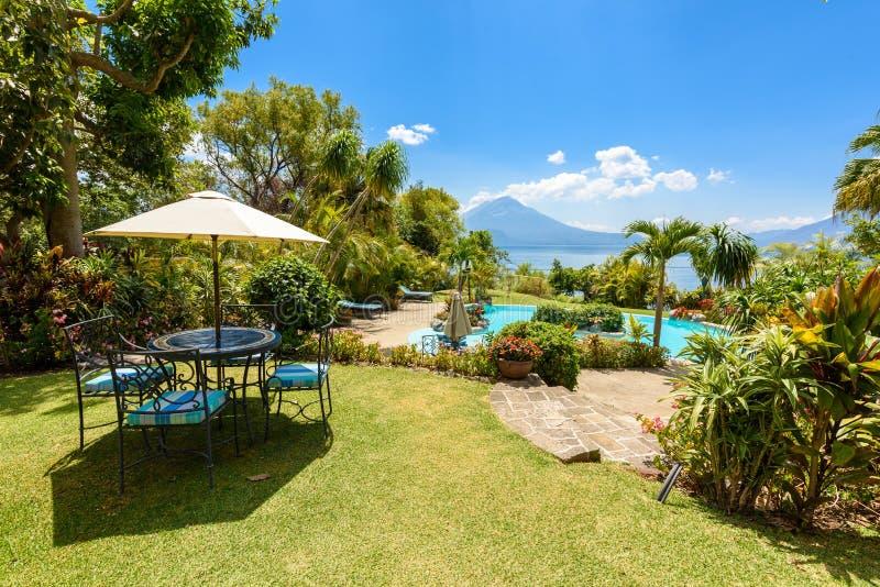 Raj plaża z krzesłem przy jeziornym Atitlan, Panajachel - Relaksować i odtwarzanie z vulcano kształtujemy teren scenerię w średni zdjęcie royalty free