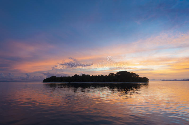 Raja Ampat Island at Sunset. There are around 1,500 uninhabited and remote islands in the Raja Ampat area of eastern Indonesia. This one is featured during a royalty free stock photo