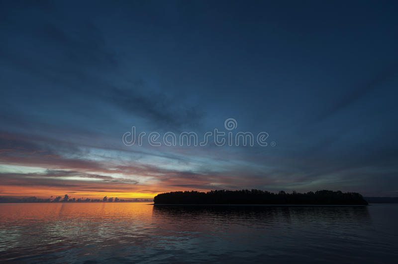 Raja Ampat Island at Sunset. There are around 1,500 uninhabited and remote islands in the Raja Ampat area of eastern Indonesia. This one is featured during a royalty free stock photos