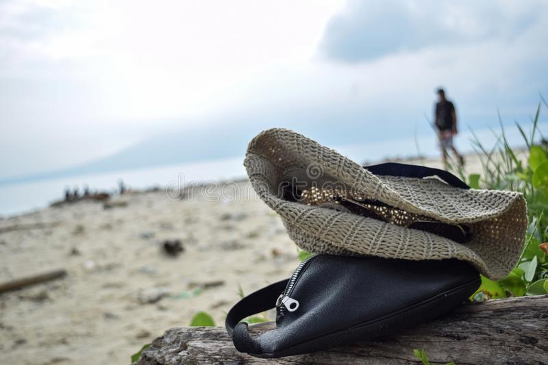 Black waist bag and hat fabrics on shore in Sebesi island, Indonesia royalty free stock photography