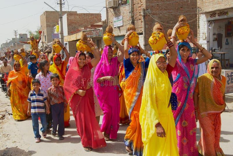 Rajasthani kvinnor som bär gula och röda sarees som rymmer kokosnötter och krukor, tar delen i en religiös procession i Bikaner,  arkivbild