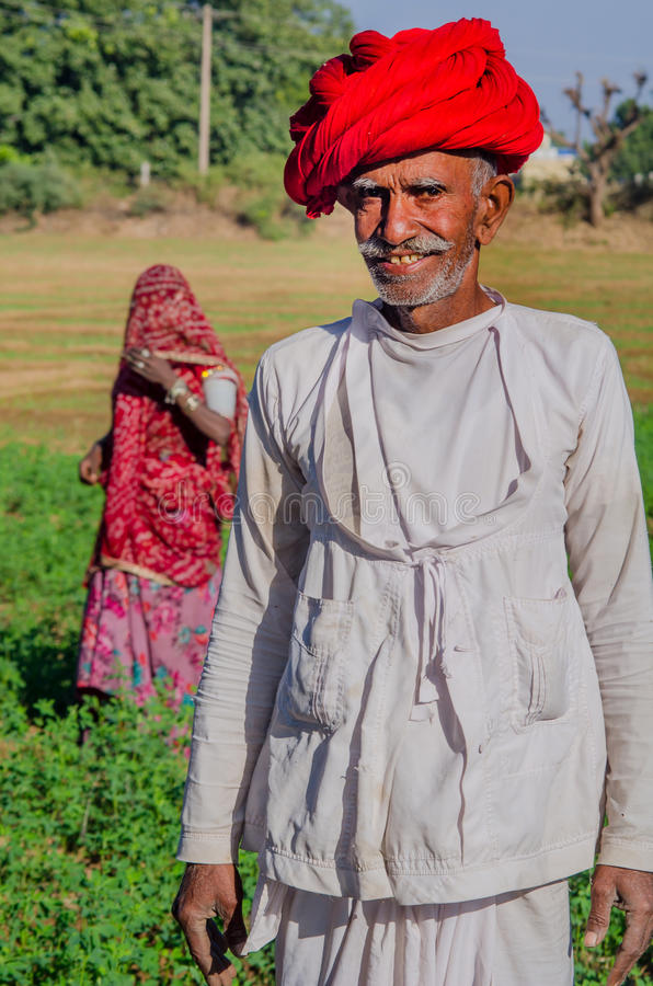 Rajasthani senior man. Rajasthan, India - November 20, 2016: Rajasthani senior man wearing red turban and traditional dress in farm with his wife in backgrouund royalty free stock photo
