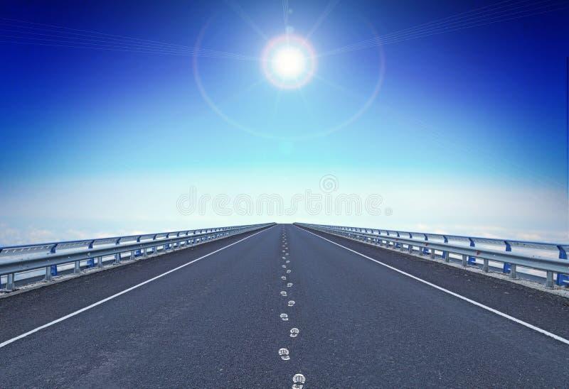 Rak motorway med fotspår och en vägleda stjärna över horisont royaltyfri foto