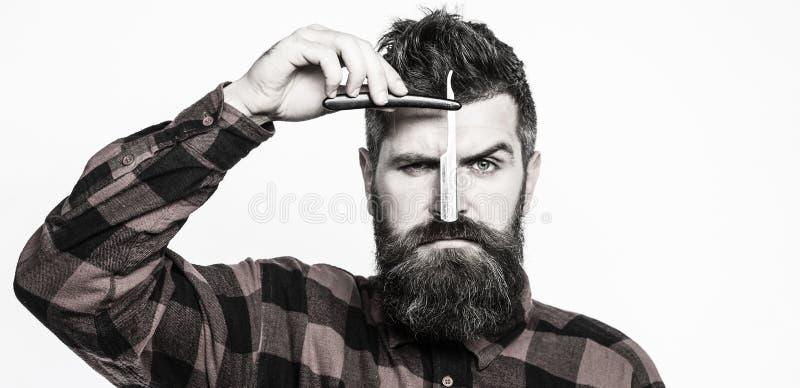 Rak rakkniv för tappning Frisersalongservicebegrepp Den stiliga skäggiga frisören rymmer en stund för rak rakkniv royaltyfri foto