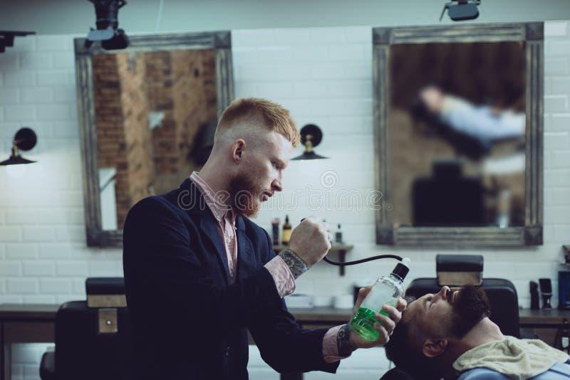Rakblad Skäggig man som får frisyr av frisören och sitter i stol på frisersalongen  Män arkivfoton