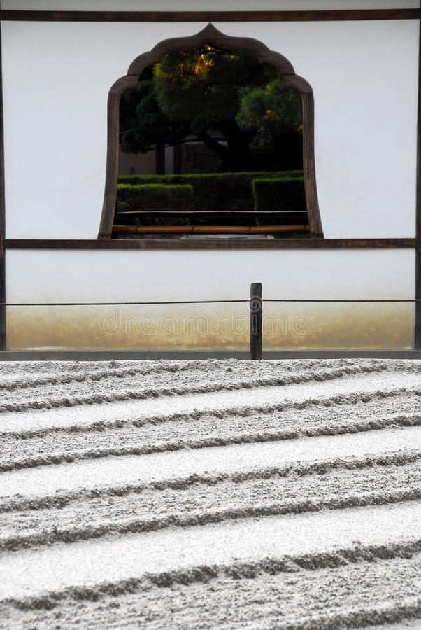 Raked sand lines and window. Raked sand and gravel resulting in parallel lines and traditional cusped window at the Buddhist temple Ginkakuji, Silver Temples in royalty free stock photo