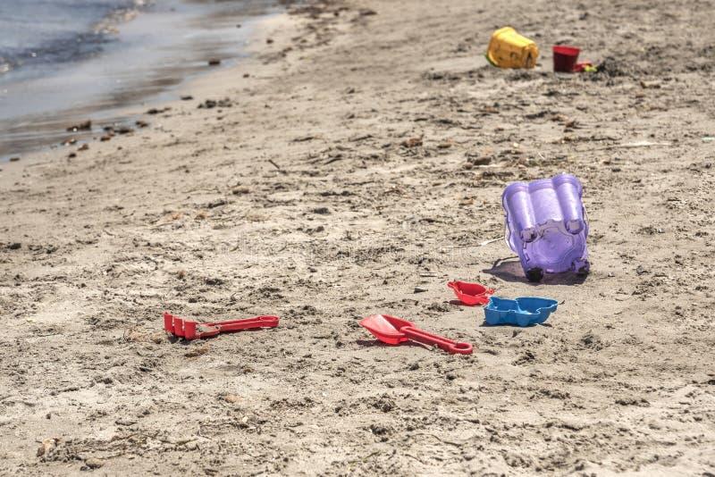 Raker e colher plásticos losted das cubetas da areia de uma criança na praia Dia ensolarado no mar Mediterr?neo foto de stock