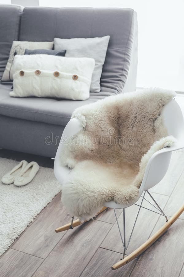 Raketstol med får flår filten i scandinavian vardagsrum royaltyfria foton
