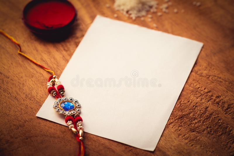 Rakhi With Kumkum, Rice Grains And A White Paper On A Wooden Surface royalty free stock image