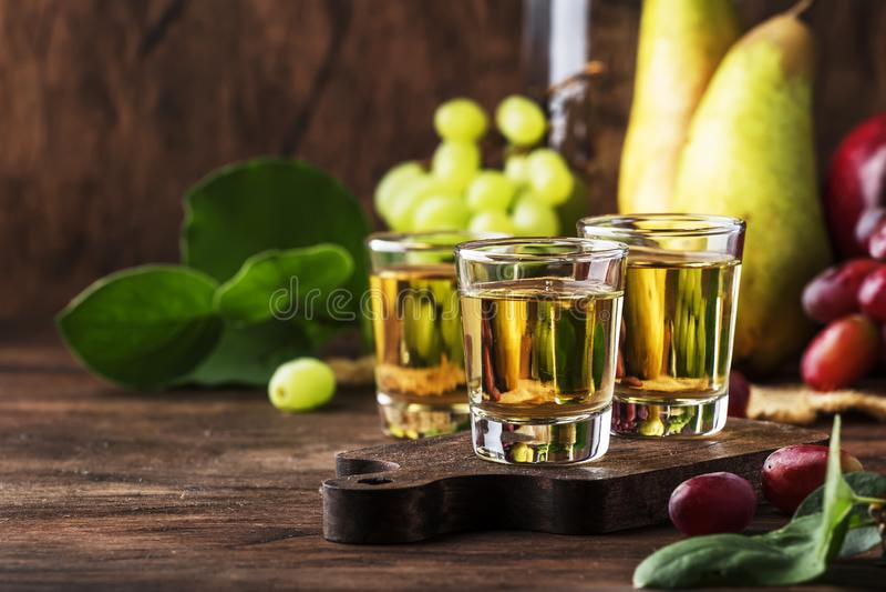 Rakija、raki或者rakia -根据被发酵的果子的巴尔干强的酒精饮料白兰地酒类型,葡萄酒木桌,静物画  免版税库存图片