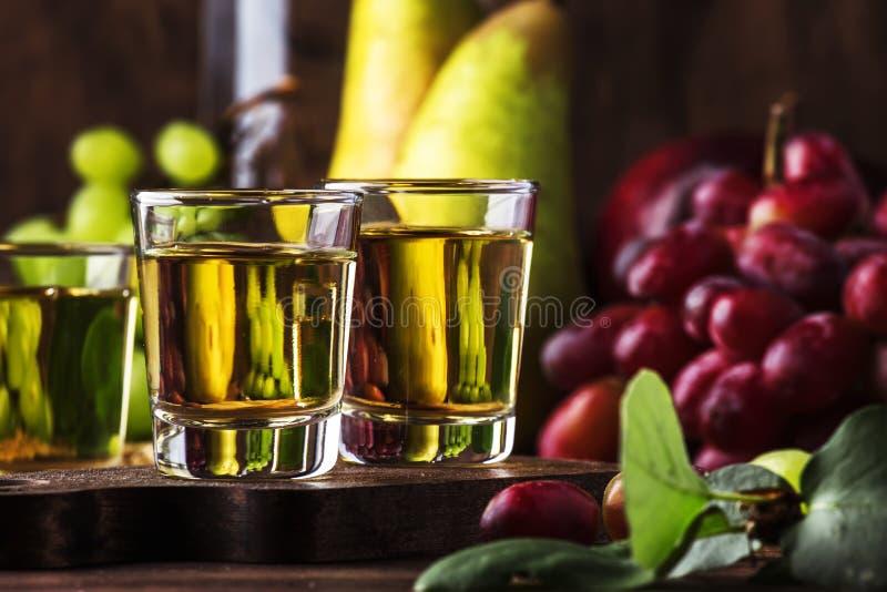 Rakija, raki eller rakia - Balkan stark alkoholdryckkonjaktyp som in baseras på jäste frukter, tappningträtabell, stilleben royaltyfri fotografi