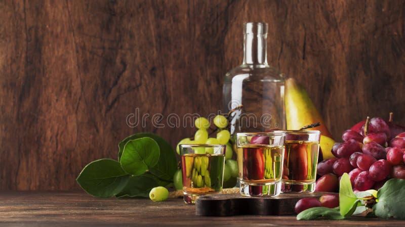 Rakija, raki o rakia - tipo fuerte balcánico basado en las frutas fermentadas, tabla de madera del vintage, aún vida del brandy d foto de archivo libre de regalías