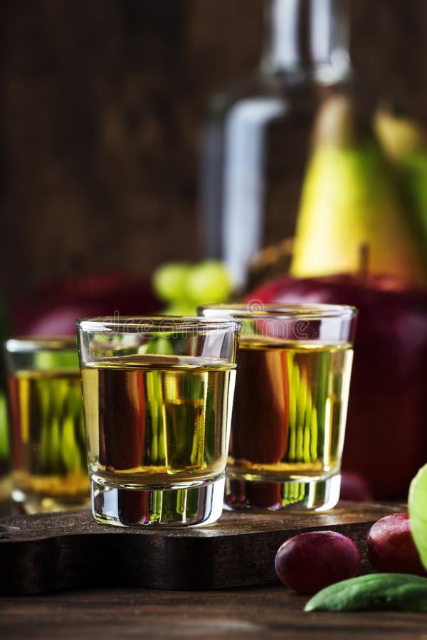 Rakija, raki or rakia - Balkan strong alcoholic drink brandy type based on fermented fruits, vintage wooden table, still life in. Rustic style, place for text stock images