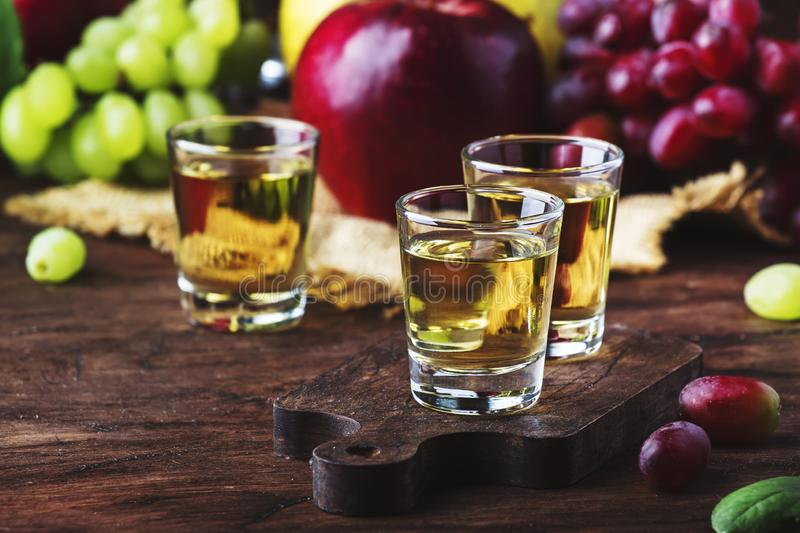 Rakija, raki or rakia - Balkan strong alcoholic drink brandy type based on fermented fruits, vintage wooden table, still life in. Rustic style, place for text royalty free stock photography