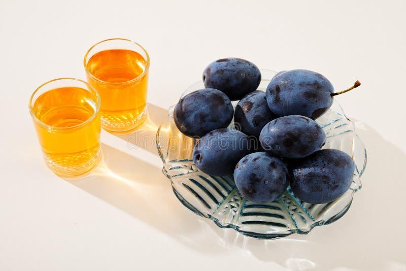 Rakija. Two glasses with rakija and plums in glass plate, isolated on white background stock image