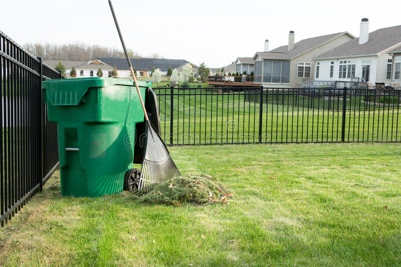 Raking lawn clippings on a suburban estate royalty free stock photos
