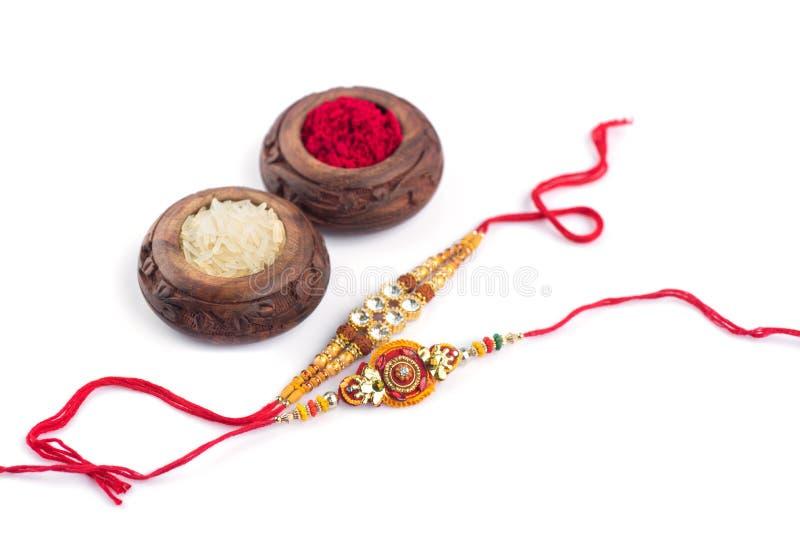 Raksha Bandhan-achtergrond met een elegante Rakhi, Rijstkorrels en Kumkum op een witte achtergrond Een traditionele Indische whi  royalty-vrije stock afbeeldingen