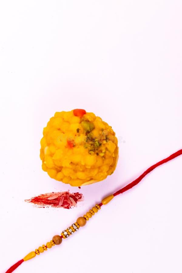 Raksha Bandhan Festival – Dichte mening van elegante Rakhi, snoepjes, blauw giftvakje, en Indische muntnota's met kumkum en rijst stock afbeelding
