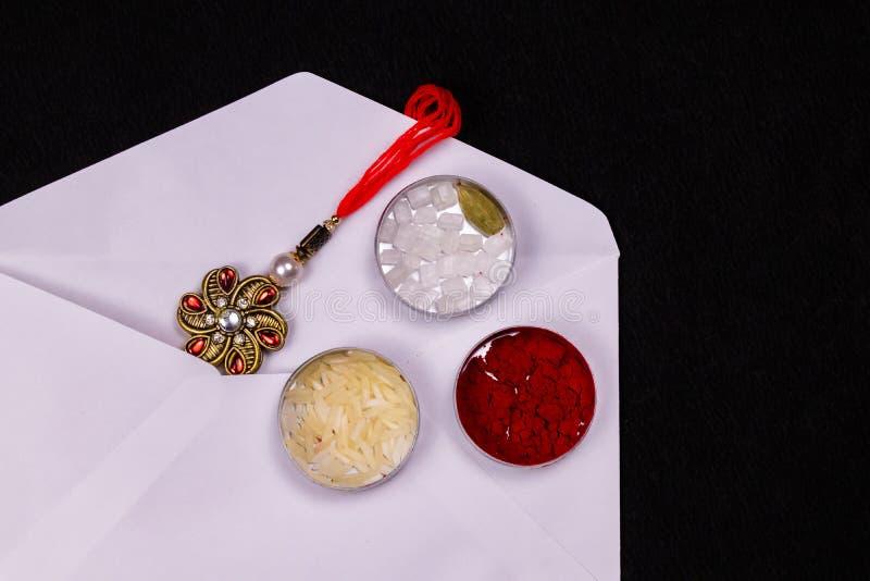 Raksha Bandhan Festival – Dichte mening van elegante Rakhi, snoepjes, blauw giftvakje, en Indische muntnota's met kumkum en rijst stock fotografie