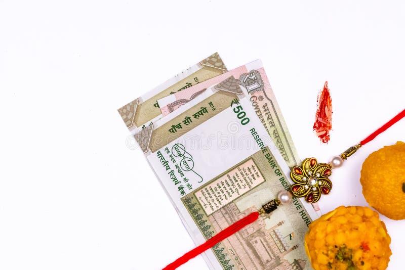 Raksha Bandhan Festival – Dichte mening van elegante Rakhi, snoepjes, blauw giftvakje, en Indische muntnota's met kumkum en rijst royalty-vrije stock afbeeldingen