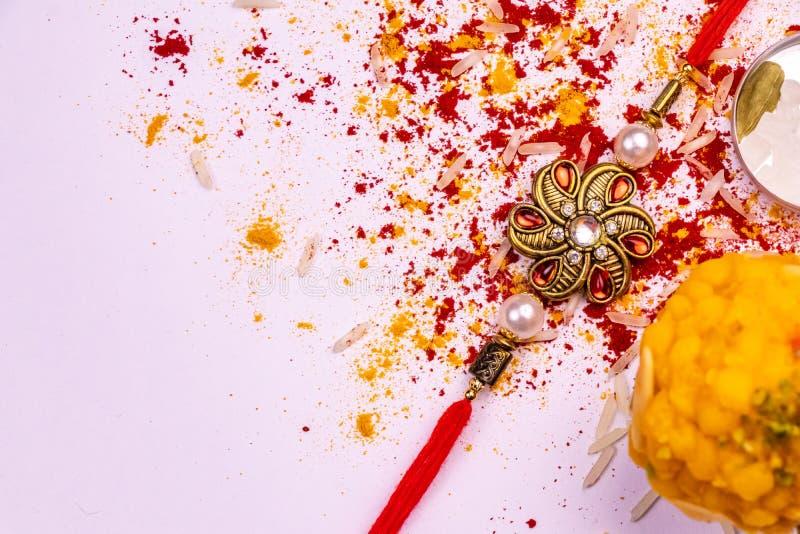 Raksha Bandhan Festival – Dichte mening van elegante Rakhi, snoepjes, blauw giftvakje, en Indische muntnota's met kumkum en rijst royalty-vrije stock afbeelding