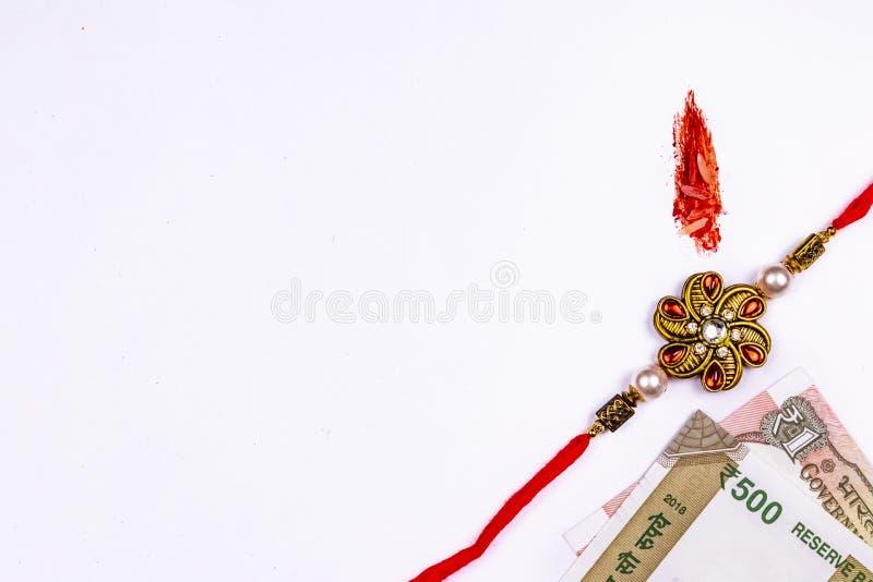 Raksha Bandhan Festival – ideia próxima de Rakhi elegante, de doces, da caixa de presente azul, e de notas indianas da moeda com  fotos de stock royalty free