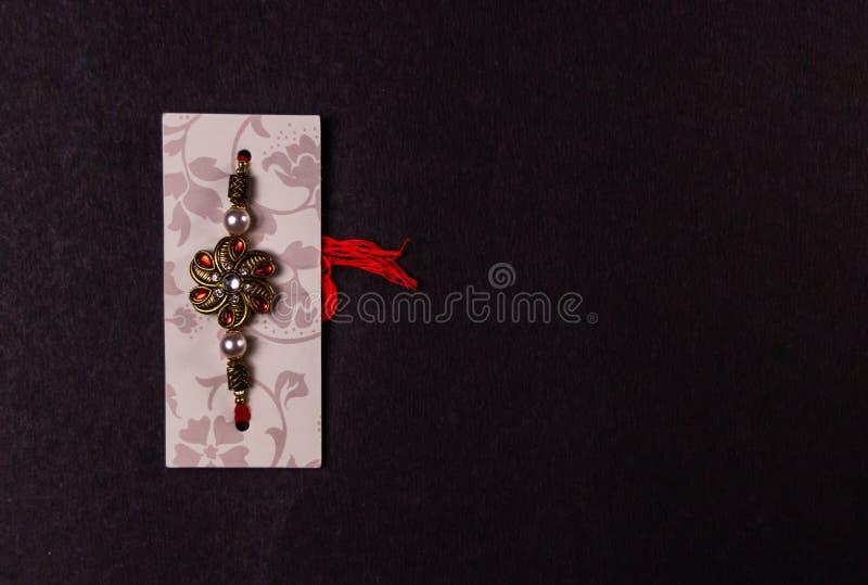 Raksha Bandhan-festivalconcept - Ontwerper Rakhi of Polsband die op zwarte achtergrond wordt geïsoleerd Rakhi - Symbool van liefd stock foto