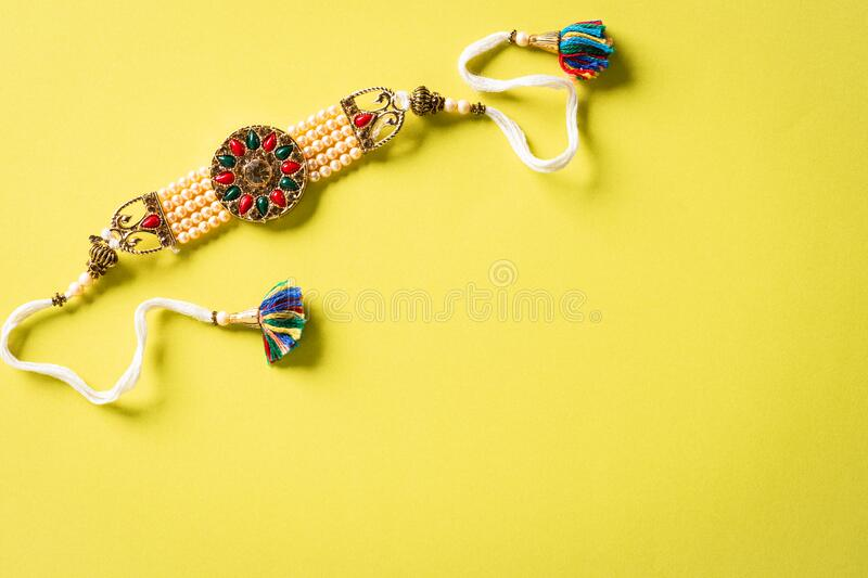 Raksha Bandhan, Indian festival with beautiful Rakhi and Rice Grains on yellow background. A traditional Indian wrist band which. Is a symbol of love between stock photography