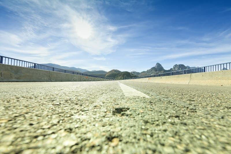 Raksträcka på en väg mellan berg med den främsta solen fotografering för bildbyråer