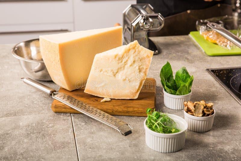 Ralador raspado do queijo parmesão e do metal na placa de madeira com hortaliças foto de stock