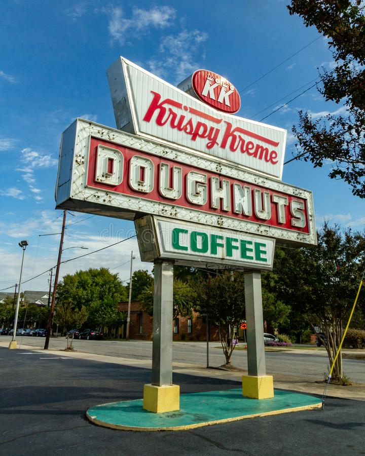 Raleigh, NC / Stati Uniti - PTOM 12.2019: Immagine verticale di tre quarti dell'iconica neon Krispy Kreme Sign durante il giorno immagini stock libere da diritti