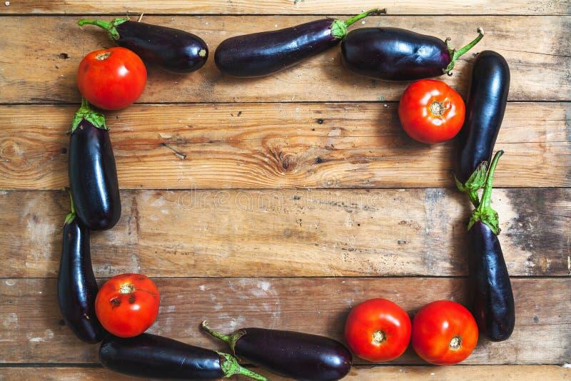 Ram av blåa aubergine och tomater på träbräden arkivfoto