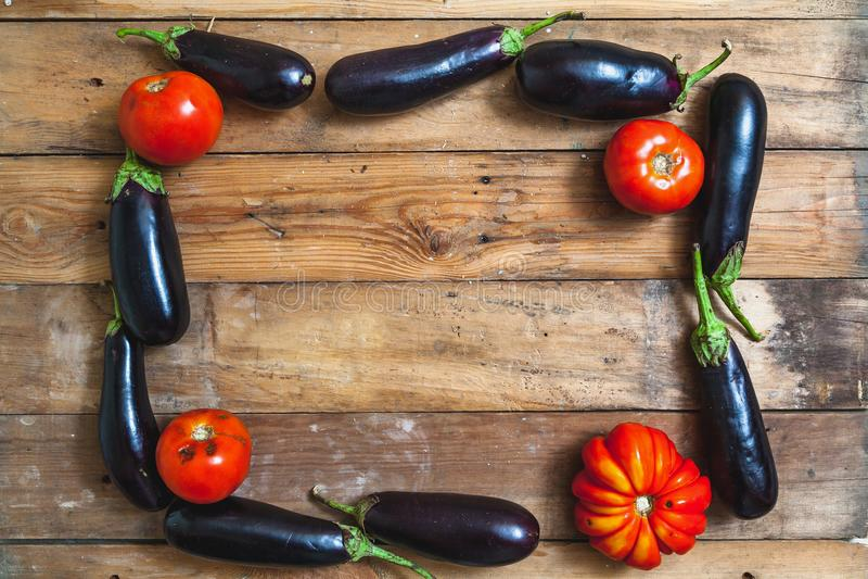 Ram av blåa aubergine och tomater på träbräden fotografering för bildbyråer