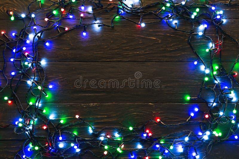 Ram av färgglade girlandljus på träbakgrund arkivbild