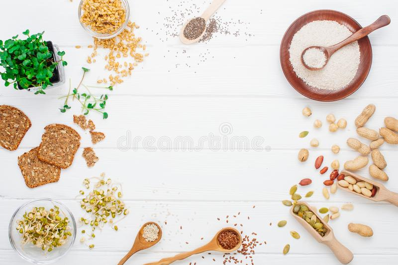 Ram av frö, rädisagroddar, bönor, muttrar och knäckebröd, havrekli på vit träbakgrund royaltyfri fotografi