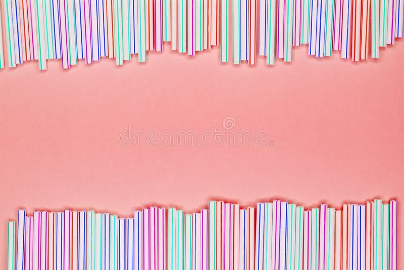 Ram av mångfärgade randiga plast- sugrör på en rosa bakgrund för korall med kopieringsutrymme ?teranv?ndning av avfalls arkivbilder