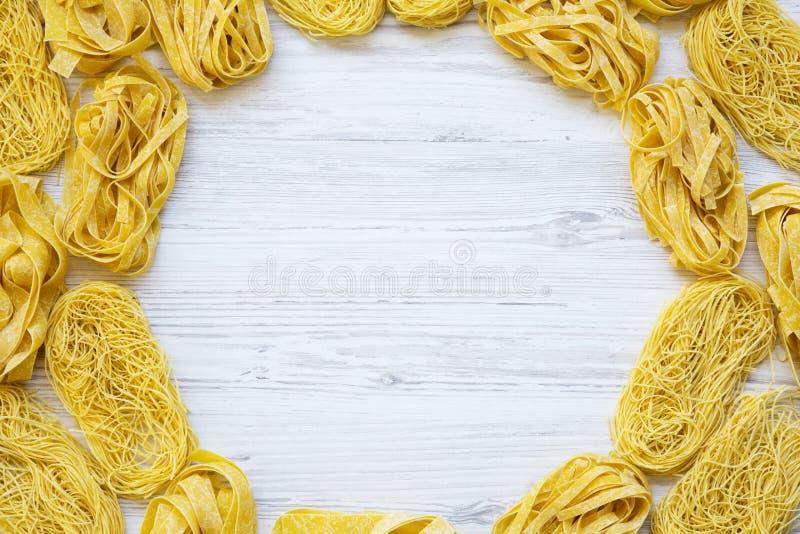 Ram av olik okokt pasta på vit träbakgrund, bästa sikt arkivbild