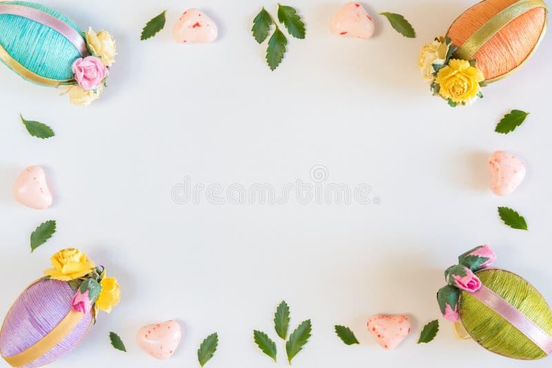 Ram av påskägg, sidor och godisen på såld vit bakgrund royaltyfri fotografi