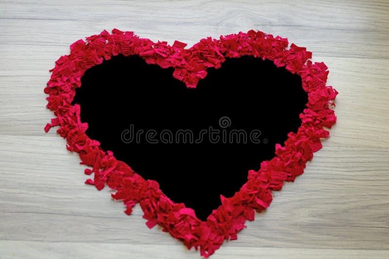Ram av röda konfettier - hjärtaform svart kopieringsutrymme, arkivbild