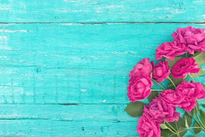 Ram av rosor på lantlig träbakgrund för turkos Vårflo royaltyfri bild