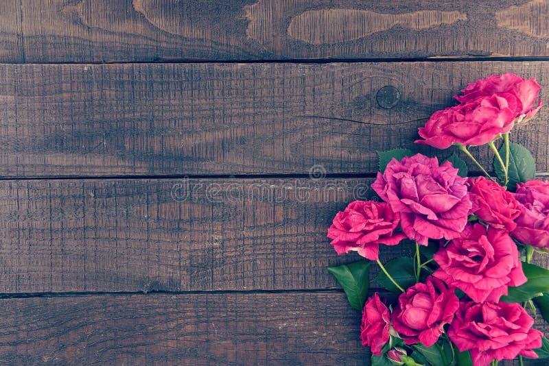 Ram av rosor på mörk lantlig träbakgrund just rained royaltyfri bild