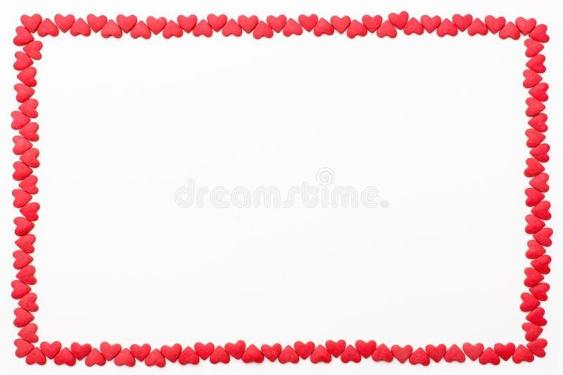 Ram av små röda hjärtor på en vit bakgrund Festlig bakgrund för dagen för valentin` s, födelsedag, bröllop, ferie, vykort, medelt arkivbilder