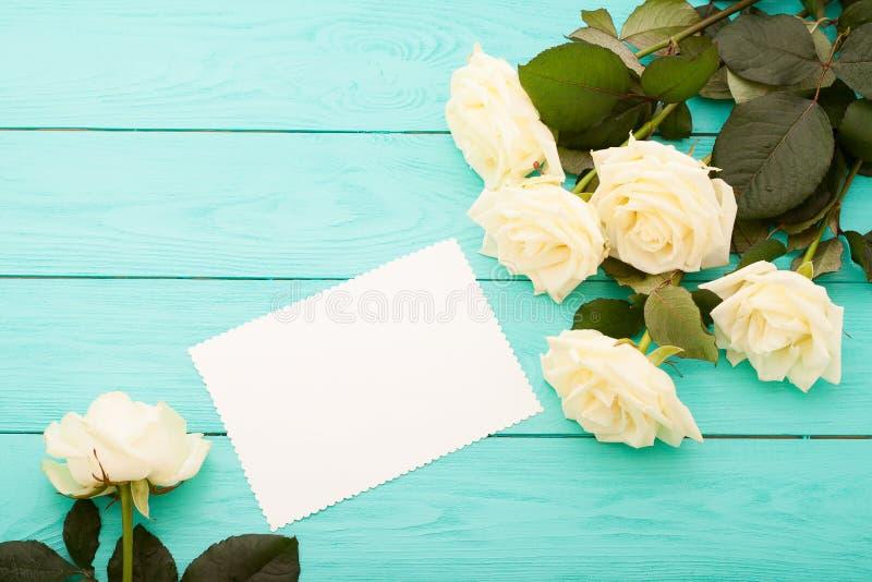 Ram av vita rosor på blå träbakgrund med utrymme för pappers- kort och kopierings Bästa sikt och selektiv fokus Åtlöje upp fotografering för bildbyråer