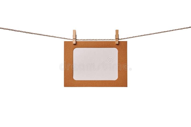 Ram för hantverkpappersfoto som hänger på repet som isoleras på vit bakgrund arkivfoton