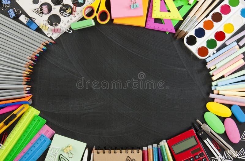 Ram för skolatillförsel på en svart tavlabakgrund royaltyfri bild