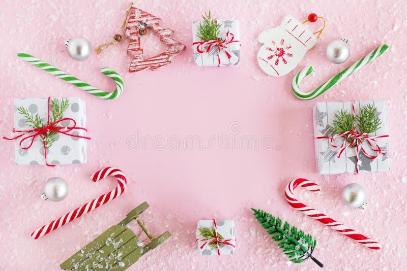 Ram från färgrikt julpynt, karamellpinnar och gåvaaskar med konstgjord snö på en rosa bakgrund arkivfoton